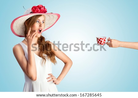 A photo of a pin-up girl in vintage hat excited of seeing a hand with the cup. - stock photo