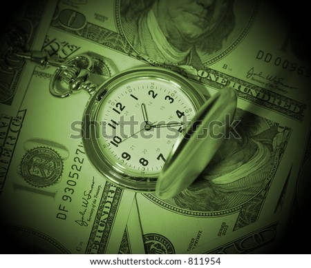 A photo of a pocket watch on hundred dollar bills