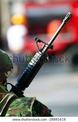 a photo of a soldier holding a machine gun - stock photo