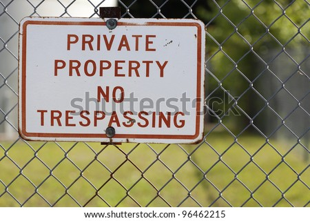 A photo of a stark red and white private property sign complete with chain link fence. - stock photo