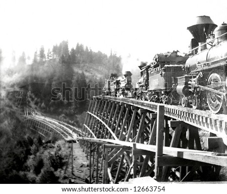 A photo of a steam engine crossing an old wooden trestle in 1890. - stock photo