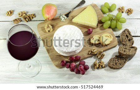 A photo of a tasting with a glass of red wine, different types of cheese, bread, nuts, pear, grapes, on a wooden board