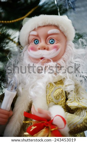 A photo of a toy Santa Claus in golden costume with an electrical candle. - stock photo