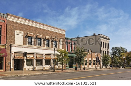 A photo of a typical small town main street in the United States of America. Features old brick buildings with specialty retail shops and restaurants. Decorated with autumn decor.  - stock photo