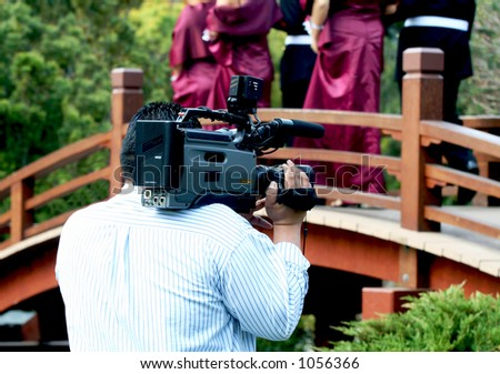 A photo of a videographer filming a wedding - stock photo