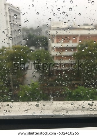 A photo of a view through out the window on the rainy day with blur background