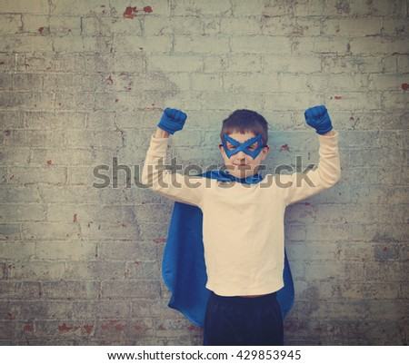 A photo of a vintage child dressed up as a super hero with his strong arms up for a confidence, bravery or imagination concept. - stock photo