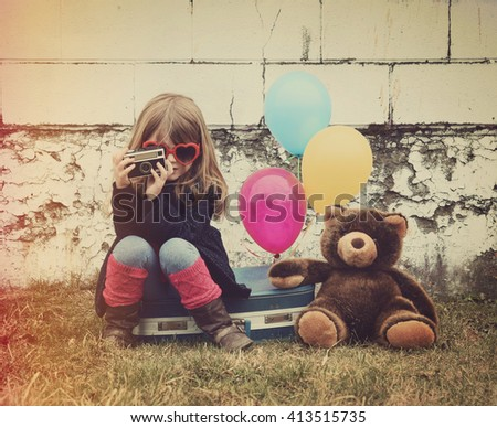 A photo of a vintage child taking a picture with an old camera against a brick wall with balloons and a teddy bear for a creativity or vision concept. - stock photo