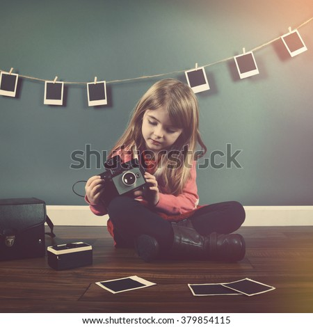 A photo of a vintage child taking a picture with an old camera with hanging pictures in the background for a creativity or art concept. - stock photo