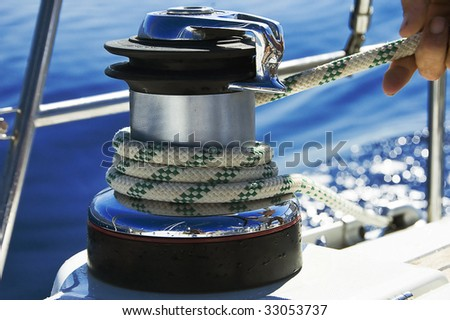 A photo of a wet rope on a boat winch being pulled in - stock photo
