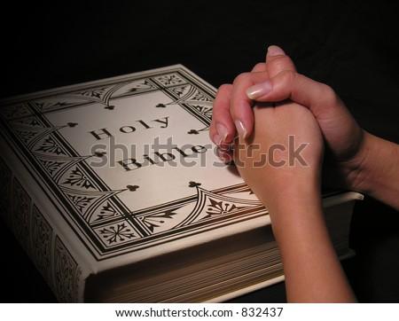 A photo of a woman praying on a bible - stock photo