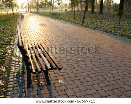 A photo of a wooden bench in park in autumn. - stock photo