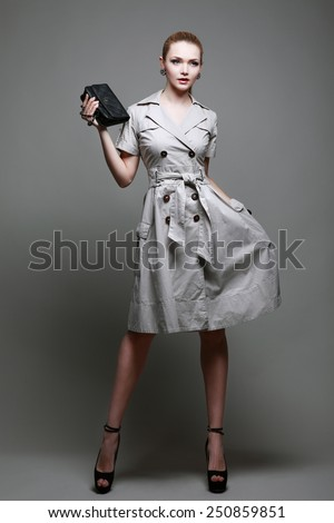 A photo of beautiful girl is in fashion style on  grey  background, glamour - stock photo