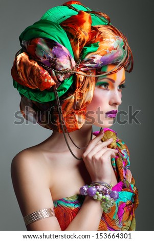 A photo of beautiful redheaded girl in a head-dress from the coloured fabric, glamour - stock photo