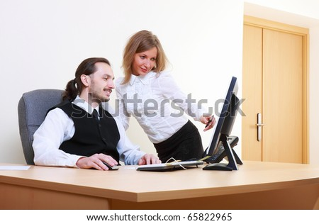 A photo of businessman working at computer, and businesswoman pointing at monitor