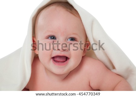 A photo of cheerful baby boy looking away Toddler is under blanket He is lying isolated over white background - stock photo