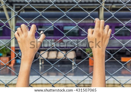 A photo of child hand hang on cage with train background, Selective focus on hand