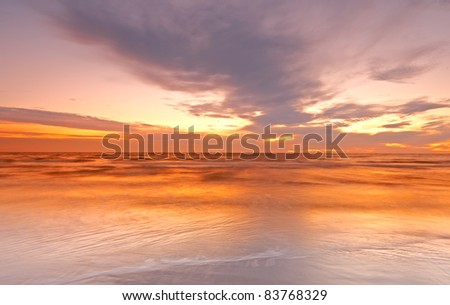 a photo of dramatic ocean sunset - stock photo