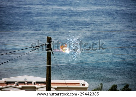 A photo of electricity wires crossing and sparking - stock photo
