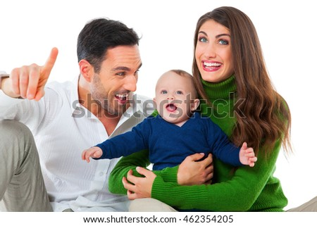A photo of happy parents playing with son. Father pointing away while looking at baby boy. They are in casuals isolated over white background.