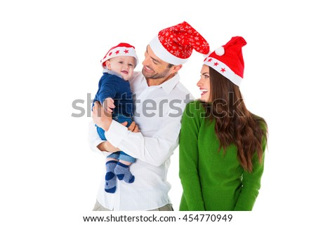 A photo of happy parents with son. Family of three are wearing Santa hats. They are in casuals isolated over white background. - stock photo