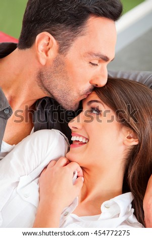 A photo of loving man kissing woman's forehead. Loving young male and female partners spending leisure time. They are at home. - stock photo