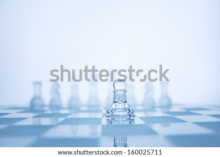 A photo of pawn standing in front of the same colour chess set. - stock photo