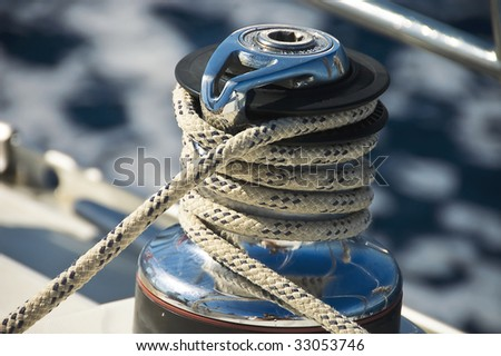 A photo of sailing boat winch with a main sail sheet rope around it - stock photo