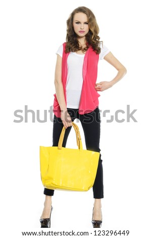 A photo of sexual beautiful girl in jeans holding yellow bag-full body - stock photo