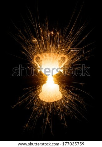 A photo of sparks flying out of a trophy in bright colors on black background with copy space. - stock photo