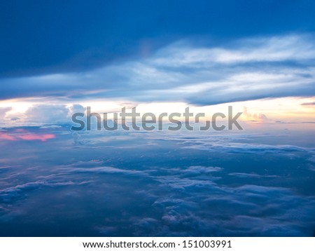 a photo of sunset above clouds from airplane window - stock photo