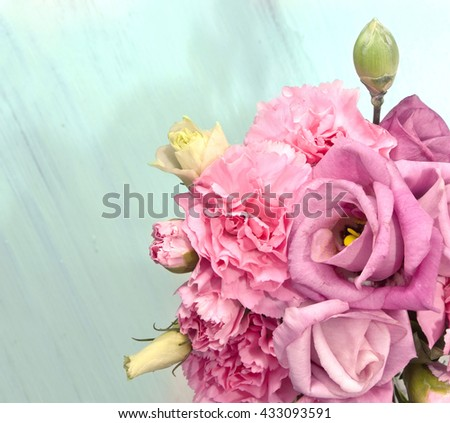 A photo of tender pink eustomas and carnations against a light teal blue wooden background, with copyspace; a greeting card or invitation template - stock photo