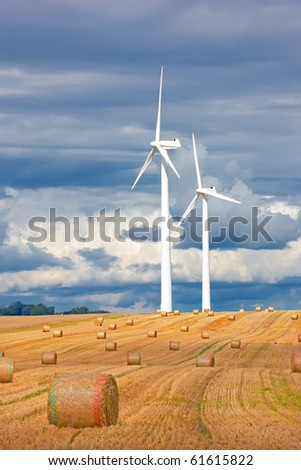 a photo of two modern windmill in countryside - harvest