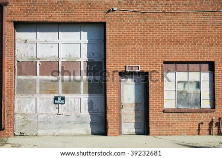A photograph of a garage door and back door in a city alley. - stock photo