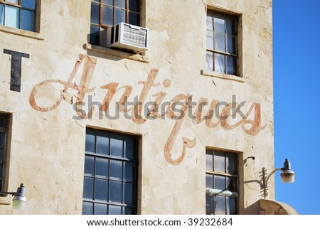 A photograph of a hand painted antique sign on the side of a business. - stock photo
