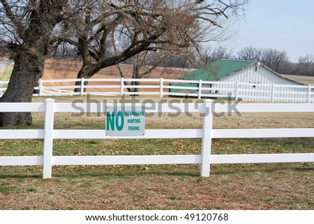 A photograph of a No Trespassing Hunting Fishing sign of a vinyl white fence with a barn in the background. - stock photo