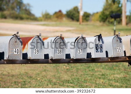 A photograph of a row of country mailboxes. - stock photo