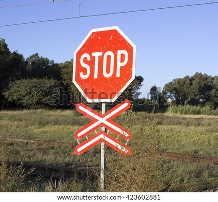 A photograph of a weathered train stop sign at an abandoned railway crossing