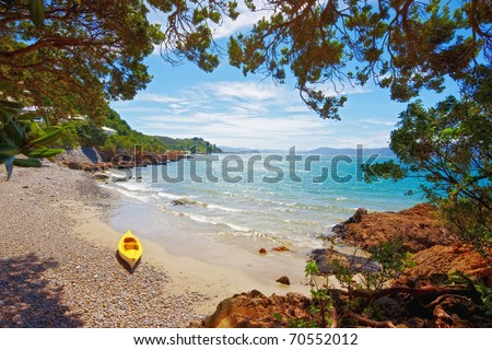 a photograph of a yellow kayak on the beach - stock photo