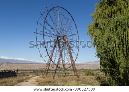 A photograph of an old and abandoned ferris wheel in Toktogul, Kyrgyzstan. - stock photo