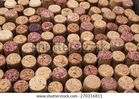 A photograph of rows of used wine corks. Some of the corks are stained from holding red wine.