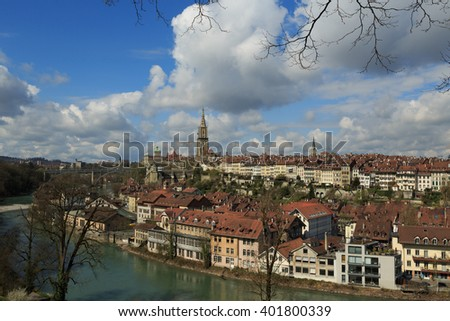 A photograph of the Old City in Bern, Switzerland, with the River Aare running around it. It is one of Switzerland's most picturesque cities. The tower of the Bern Cathedral is a prominent feature.