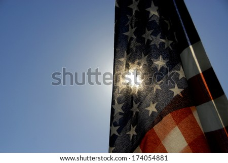 A photograph of the US flag back lit by the sun. - stock photo