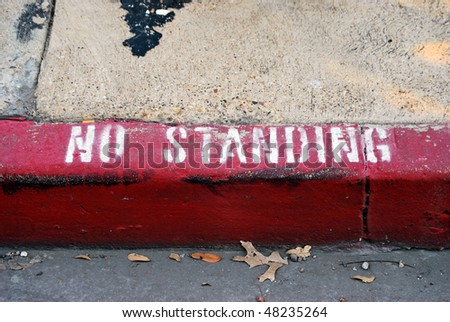 A photograph of the words No Standing painted on a city sidewalk curb. - stock photo