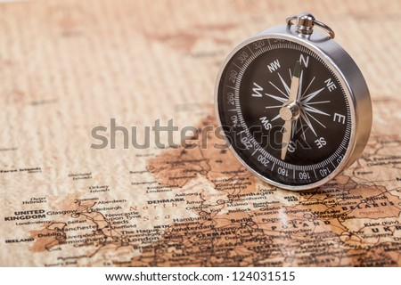 A photograph with shallow depth of field of a black compass on a map, with selective focus. - stock photo