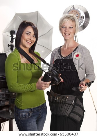 A photographer and make-up artist in the studio. - stock photo
