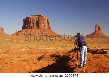 A photographer in blue jeans and dark blue vest is photographing buttes in Monument Valley park (Navajo Nation, Utah).