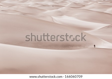 A photographer in Sand dunes setting up to take a photograph.  - stock photo