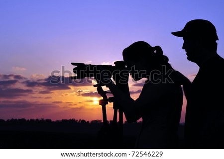 A photographer is teaching a student wildlife or landscape photography outdoors. - stock photo
