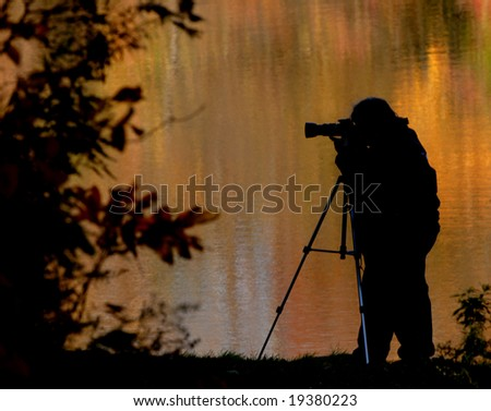 A photographer out capturing the fall colors. - stock photo